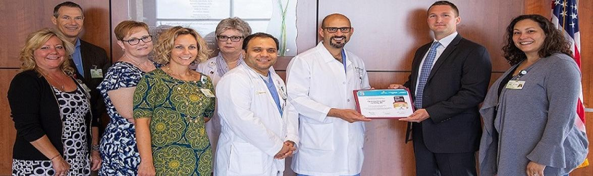 Anmar Razak, M.D., Director of the Sparrow Comprehensive Stroke Center, accepts the GOLD PLUS achievement award for Sparrow Hospital for meeting the highest level of stroke care. The award comes from the American Heart Association and American Stroke Association. Dr. Razak is surrounded by members of the Sparrow Comprehensive Stroke Center team